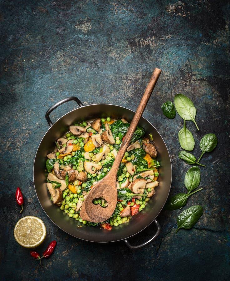 Köstliches gedämpftes gesundes Gemüse, wenn Wanne mit Bestandteilen und hölzernem Löffel auf dunklem rustikalem Hintergrund, Drau stockfoto