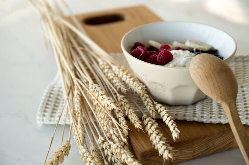 Köstliches gesundes Frühstück des Hüttenkäses mit Beeren Eine weiße Platte mit Hüttenkäse und Beerenstände auf einem hölzernen Br stockfotografie