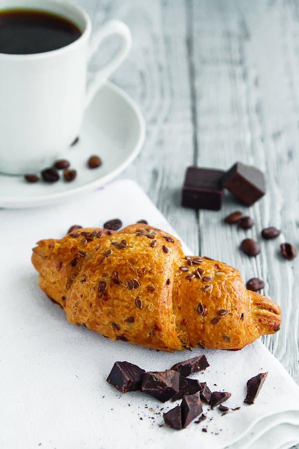 köstliches Hörnchen mit einem Tasse Kaffee auf einer hölzernen grauen Tabelle stockfoto