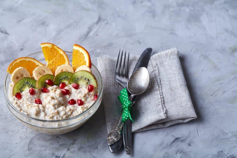 Köstliches Hafermehl mit Früchten in der Glasschüssel lokalisiert auf weißem strukturiertem Hintergrund, Kopienraum, selektiver F stockfoto