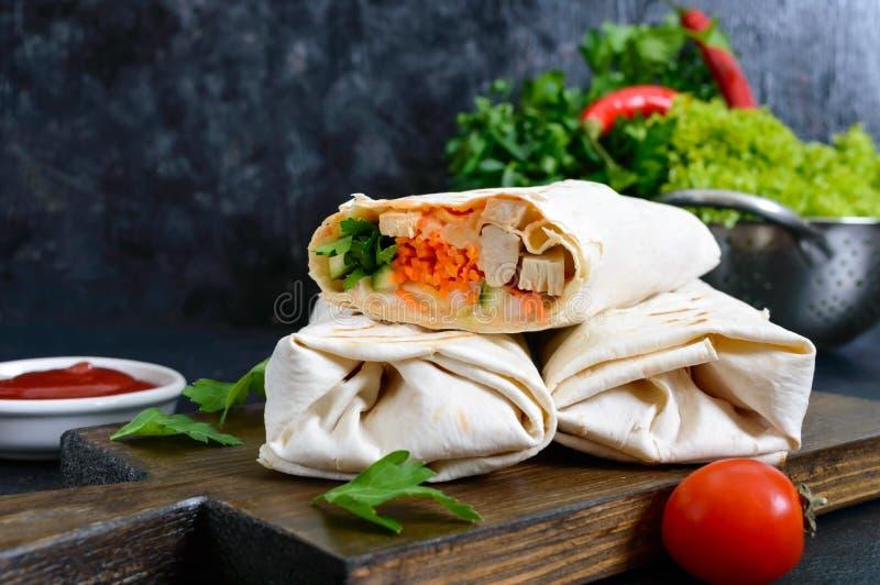 Köstliches shawarma Sandwich auf einem schwarzen Hintergrund Burritosverpackungen mit gegrilltem Huhn und Gemüse, Grüns stockfotografie