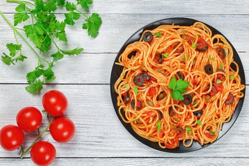 Köstliches Spaghettis alla puttanesca mit Kapriolen stockfotos