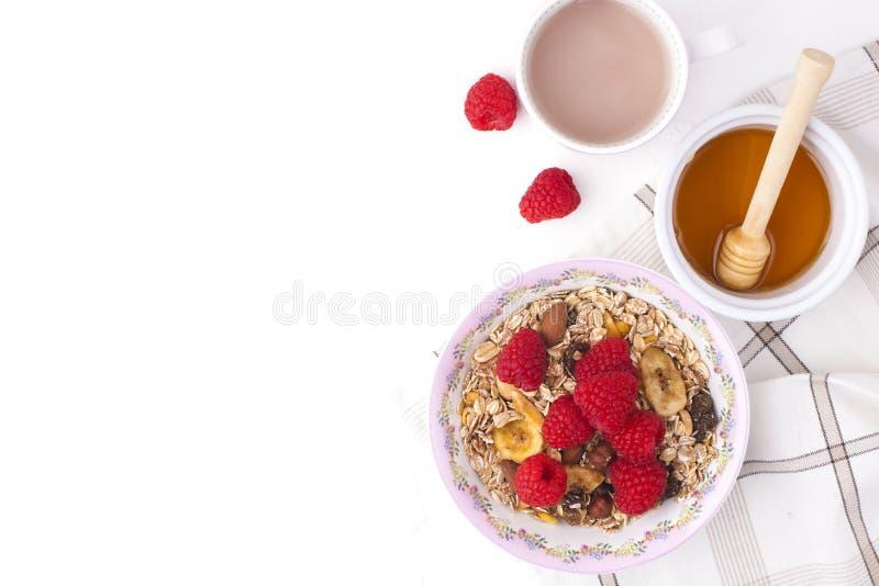 Köstliches und gesundes Frühstück auf einem weißen Hintergrund Brei des Hafermehls, Himbeere, Honig, Kaffee für einen guten Morge stockfotografie