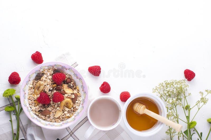 Köstliches und gesundes Frühstück auf einem weißen Hintergrund Brei des Hafermehls, Himbeere, Honig, Kaffee für einen guten Morge lizenzfreie stockbilder