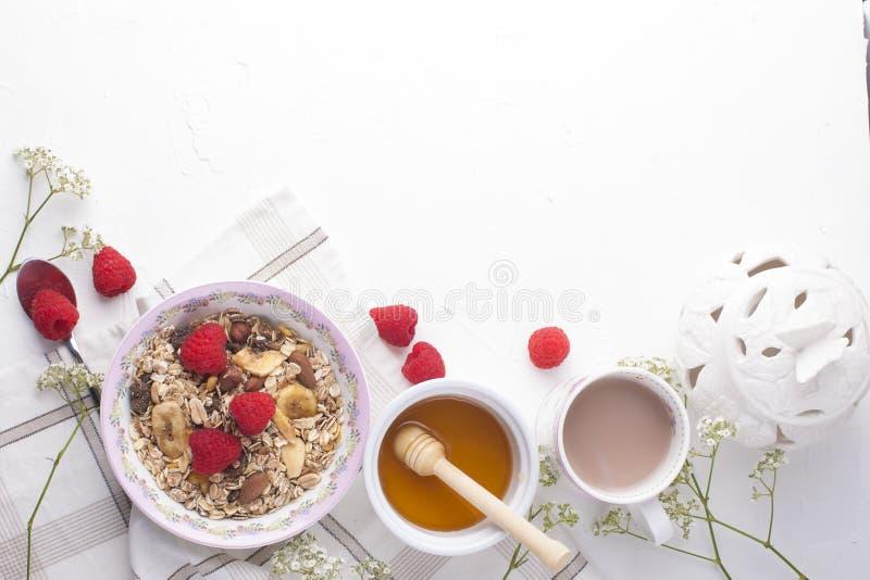 Köstliches und gesundes Frühstück auf einem weißen Hintergrund Brei des Hafermehls, Himbeere, Honig, Kaffee für einen guten Morge stockbilder