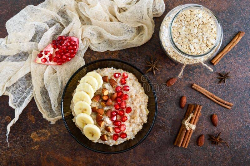 Köstliches und gesundes Hafermehl mit Banane, Granatapfelsamen, Mandel und Zimt stockfotografie