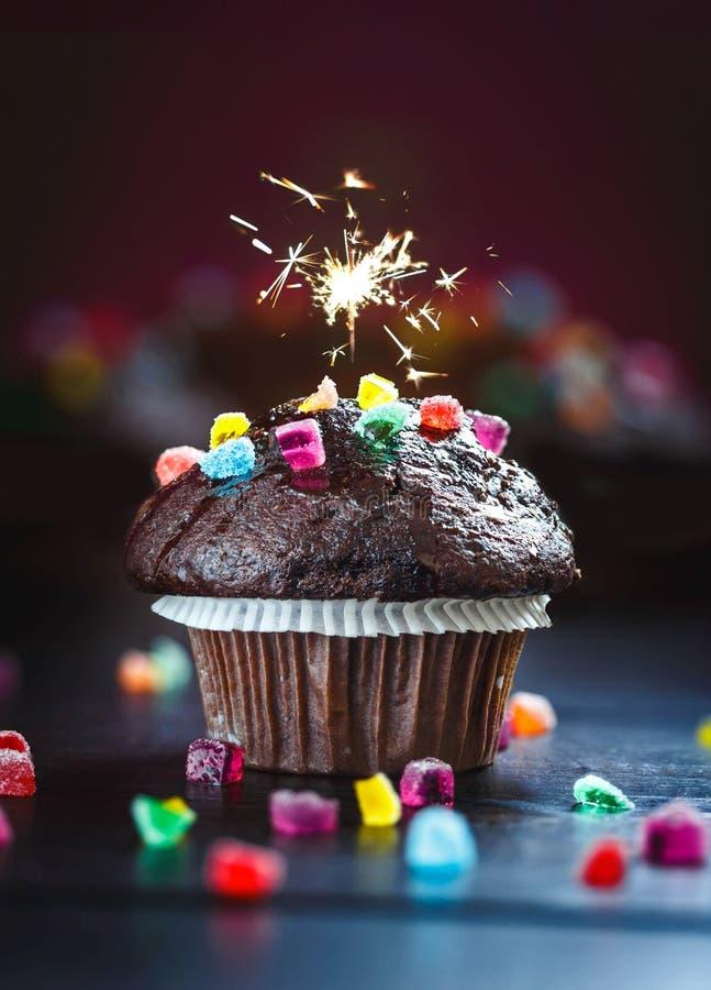 Köstliches und lustiges Schokoladen-Muffin mit Süßigkeiten und Wunderkerze lizenzfreie stockfotos