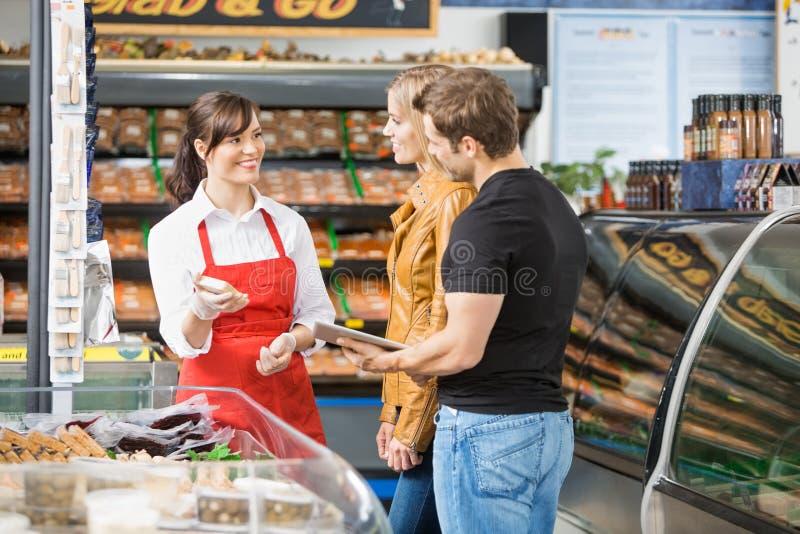 Kött för försäljareAssisting Couple In köpande arkivbilder
