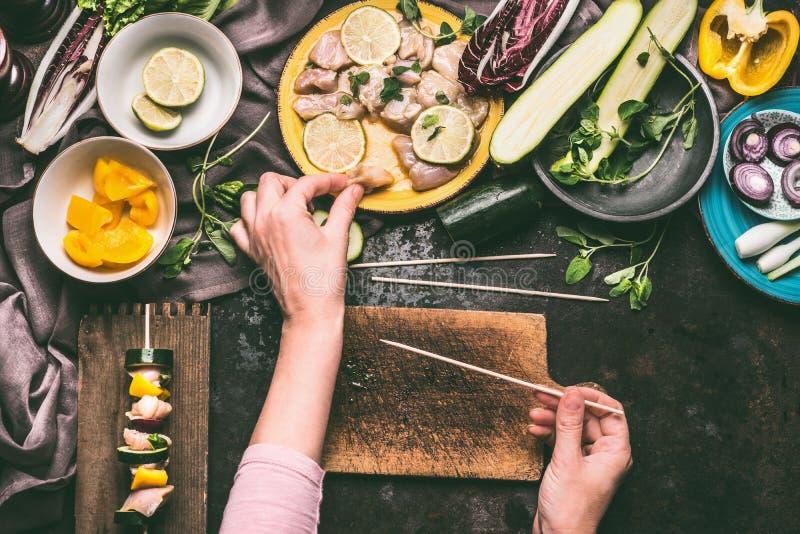 Kött- och grönsaksteknålförberedelse Den kvinnliga handen tar ett stycke av höna på mörk köksbordbakgrund med bunkar arkivfoton