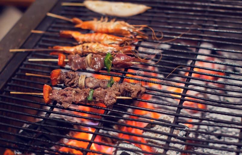 Kött och srimps på galler avfyrar att laga mat BBQ arkivfoton