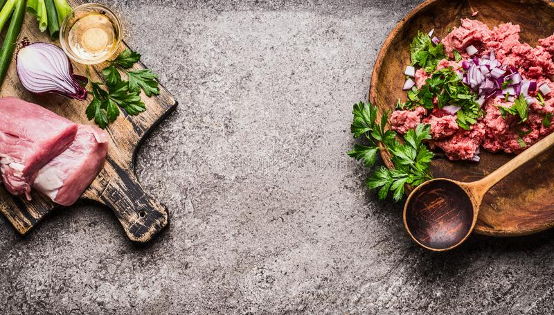 Kött på skärbräda med köttfärs, skeden och ingredienser på grå lantlig bakgrund, bästa sikt, ställe för text, ram matlagning fotografering för bildbyråer