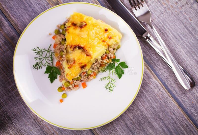 Kött, potatis, ost, morot, lök och eldfast form för gröna ärtor Traditionell herdepaj royaltyfri bild