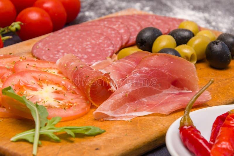 Kött som skivar med oliv och tomater, är på skärbrädan i köket royaltyfri fotografi
