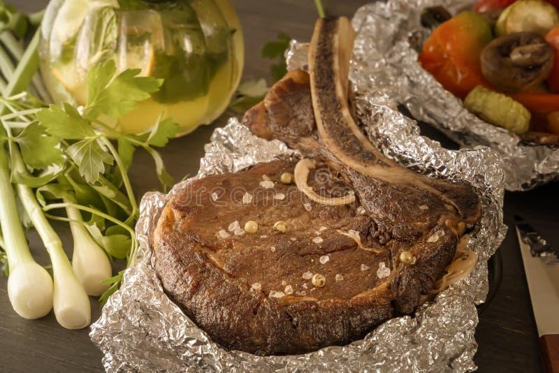 Köttbiff bakade i folie, och bakade grönsaker med ångad rånar av mintkaramelldrinken på en trätabell arkivbild