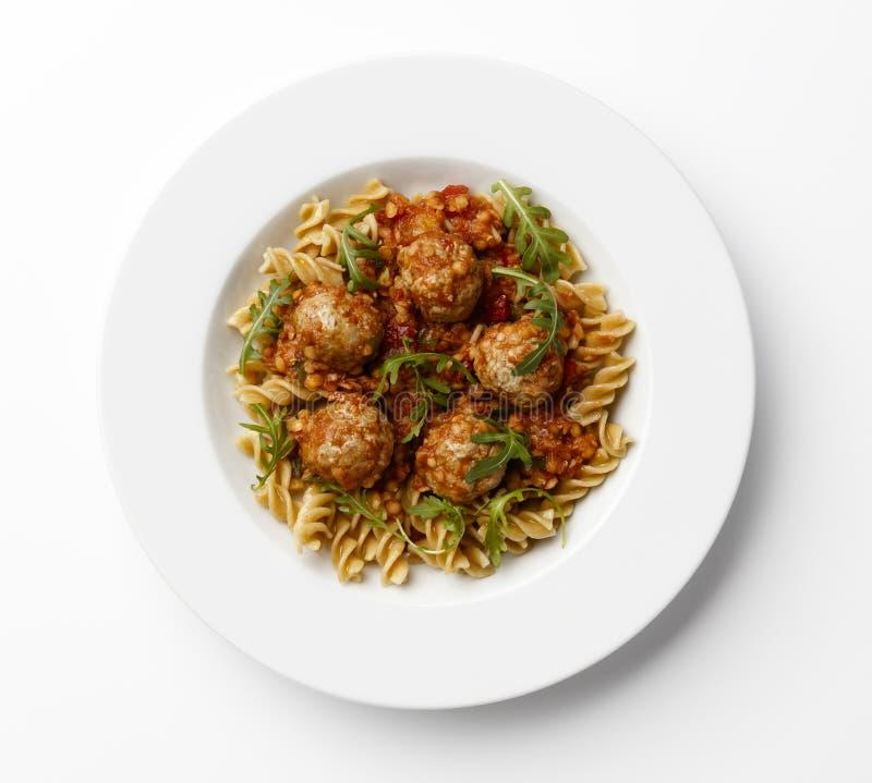 Köttbullar i en tomatsause med degvridningar med en raketgarn fotografering för bildbyråer