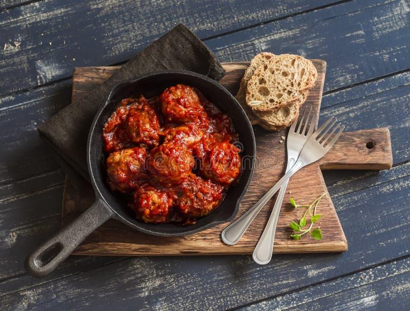 Köttbullar i tomatsås i en panna på lantlig träskärbräda arkivbilder