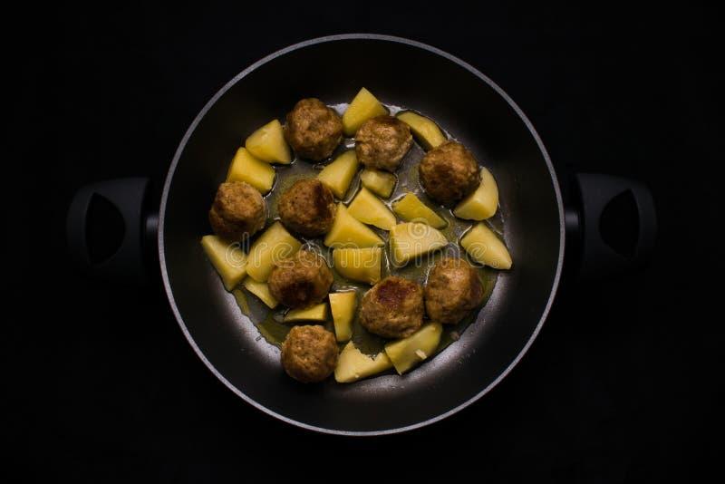 Köttbullar och potatisar i svart panna fotografering för bildbyråer