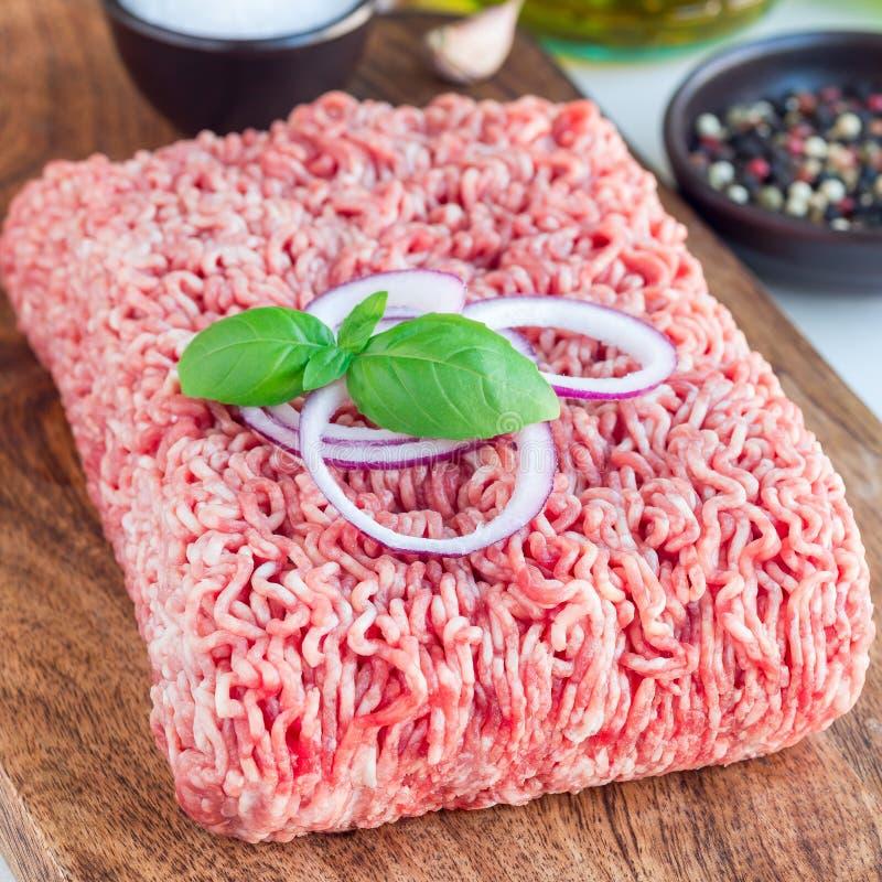 Köttfärs från griskött och nötkött Jordkött med ingredienser för att laga mat på ett träbräde, fyrkantigt format fotografering för bildbyråer
