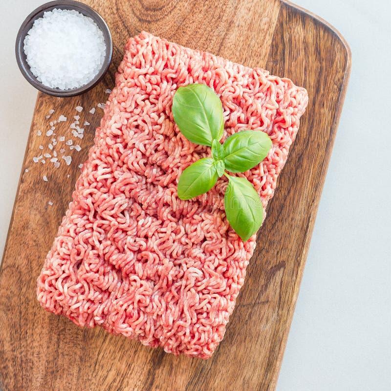 Köttfärs från griskött och nötkött Jordkött med ingredienser för att laga mat på träbrädet, bästa sikt, fyrkantigt format royaltyfri fotografi