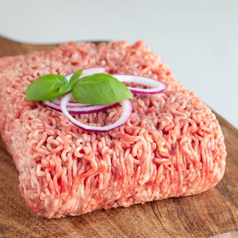 Köttfärs från griskött och nötkött Jordkött med ingredienser för att laga mat på träbrädet, fyrkantigt format royaltyfri fotografi