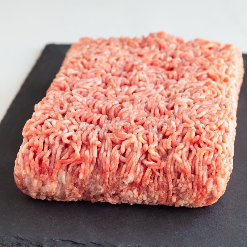 Köttfärs från griskött och nötkött, jordkött på mörker kritiserar brädet, fyrkantigt format royaltyfri fotografi
