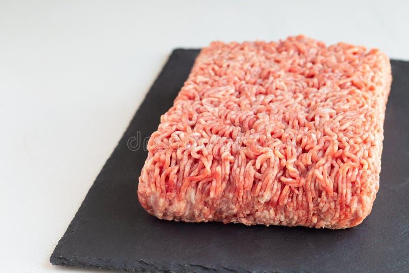 Köttfärs från griskött och nötkött, jordkött på mörker kritiserar brädet som är horisontal, kopieringsutrymme arkivbild