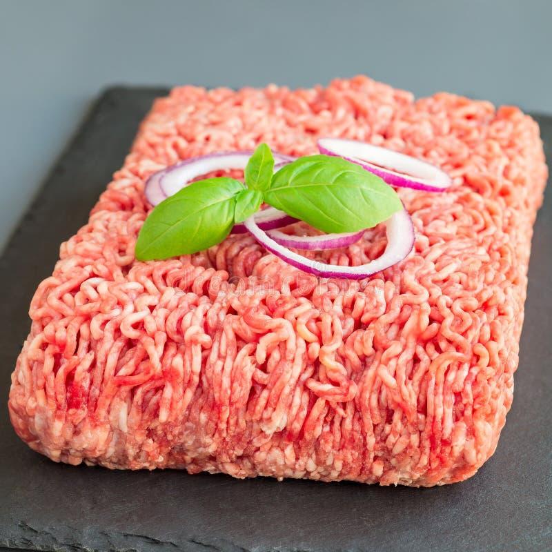 Köttfärs från griskött och nötkött Malt kött med ingredienser för att laga mat på mörker kritiserar brädet, fyrkantigt format royaltyfria foton