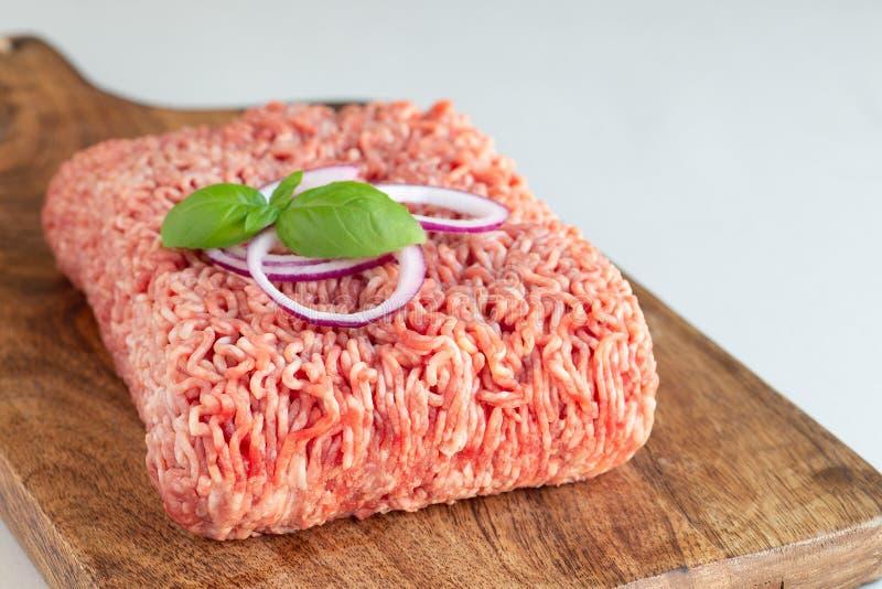 Köttfärs från griskött och nötkött Malt kött med ingredienser för att laga mat på träbräde som är horisontal, kopieringsutrymme arkivfoton