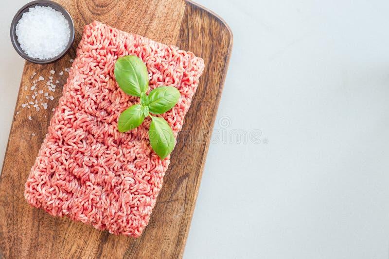 Köttfärs från griskött och nötkött Malt kött med ingredienser för att laga mat på träbrädet, horisontal bästa sikt, kopieringsutr fotografering för bildbyråer