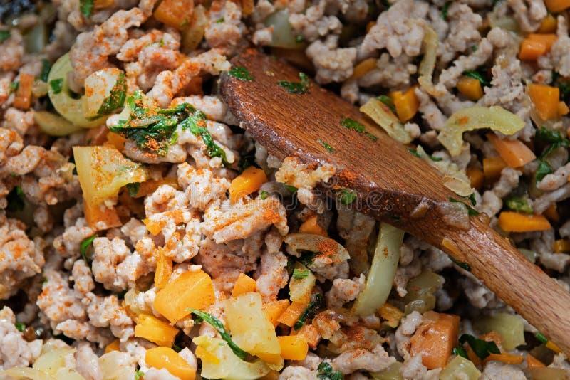 Köttfärs, morötter, paprika, persilja och kryddor blandade med att laga mat skeden arkivfoto