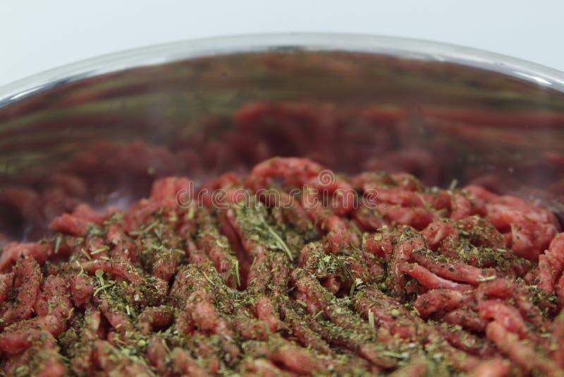 Köttfärs- och Provencal örter i en kastrull, innan att laga mat Kött och örter i en panna, innan att laga mat arkivfoto