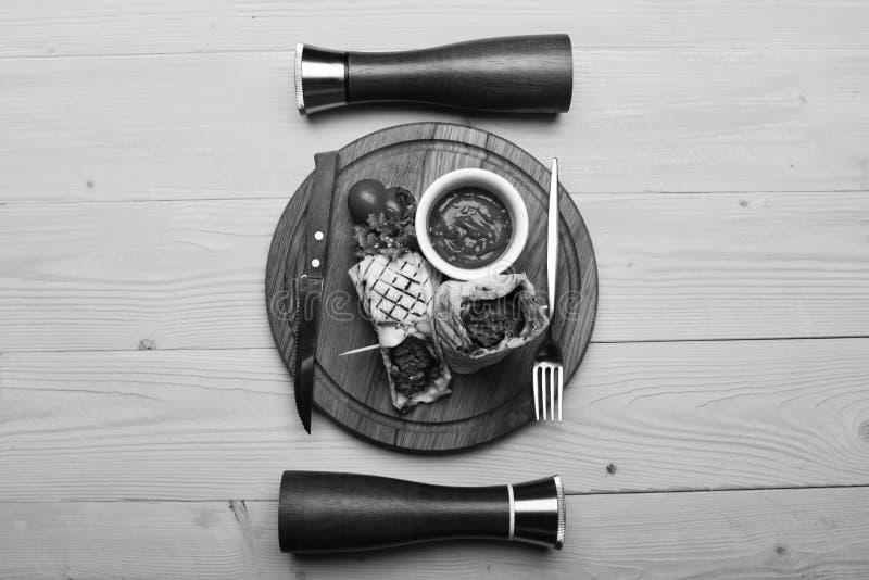 Köttfärs som slås in med lavashbröd på gul träbakgrund Tunnbröd med griskött- eller hönafyllning och röd chili royaltyfri fotografi