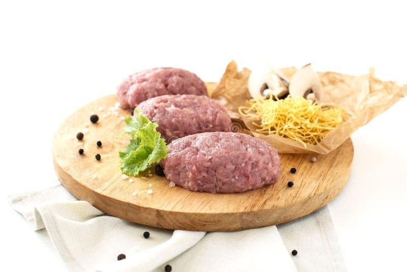 Köttfärssmå pastejer, huggit av kött som lagar mat, griskött, höna, kalkon, lök, smaktillsats på vit isolerad bakgrund royaltyfri bild