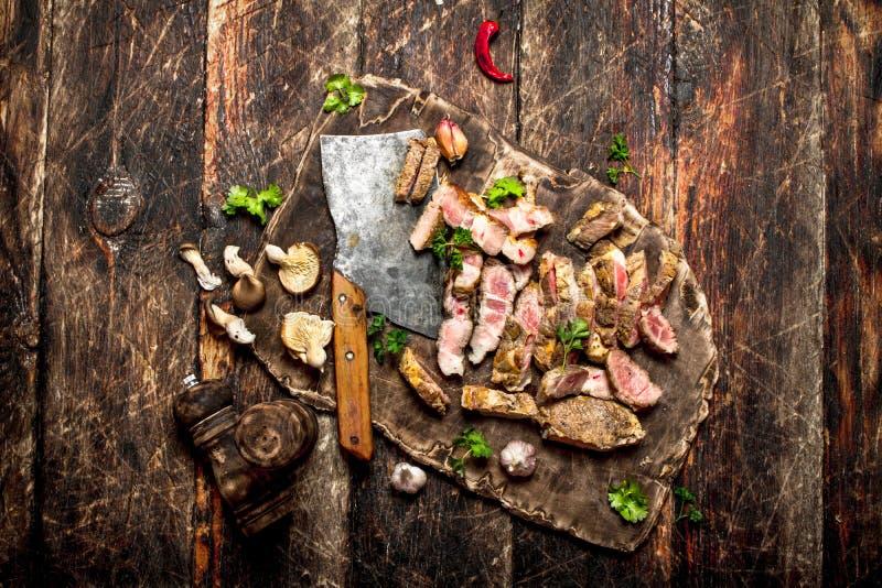 Köttgaller Sliced grillade griskött med en gammal handyxa, kryddor och örter royaltyfri fotografi