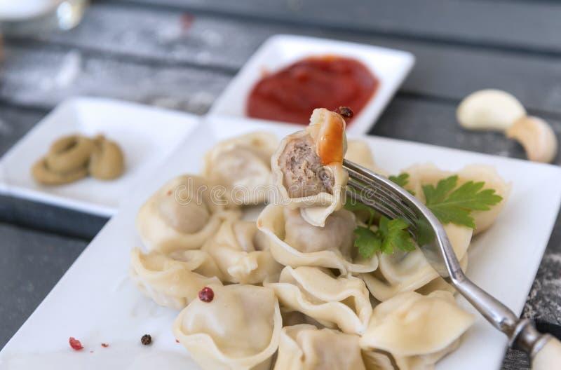 Köttklimp på en gaffel, många klimpar i en platta, ketchup, senap, vitlök arkivfoto