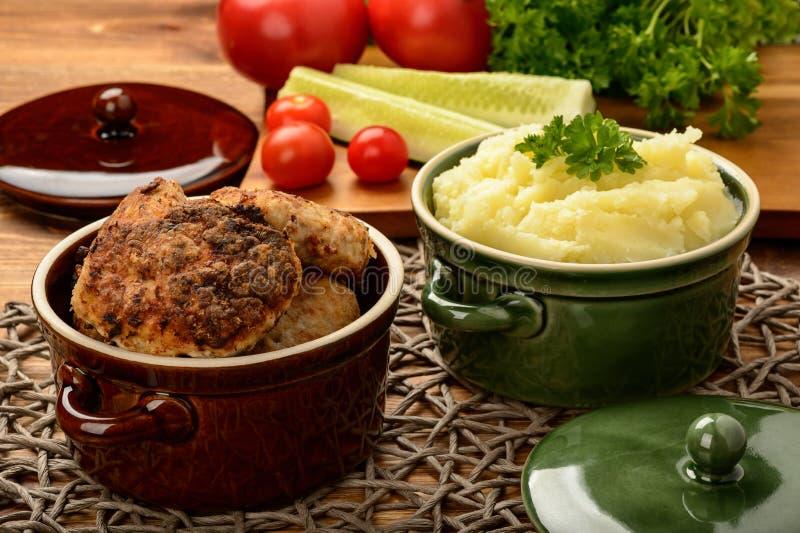 Köttkotletter och mosade potatisar i keramiska krukor arkivbilder