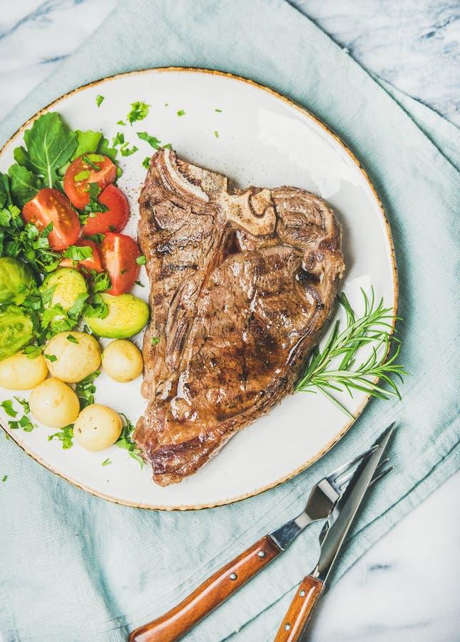 Köttmatställeplatta med lagad mat nötköttt-ben biff, bästa sikt arkivfoto