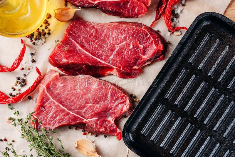 Köttnötköttbiffar som är klara att lagas mat med olivolja och kryddor royaltyfri foto