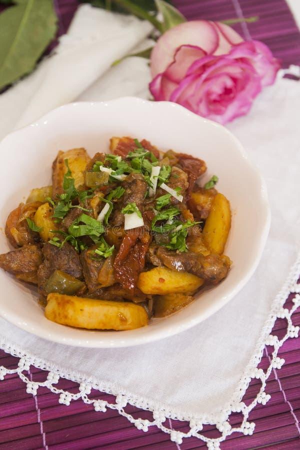 Köttragu med potatisar och kryddor, tomater, gurkor och gräsplaner goulash arkivfoton