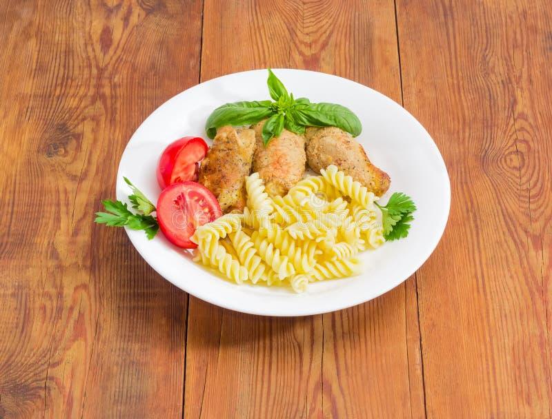 Köttroulades med fyllning, spiral pasta och tomaten arkivfoto