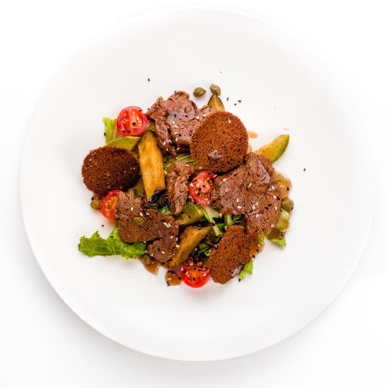 Köttsallad med steknötkött, krutonger, grönsaker och potatisar på vit bakgrund som isoleras royaltyfri fotografi
