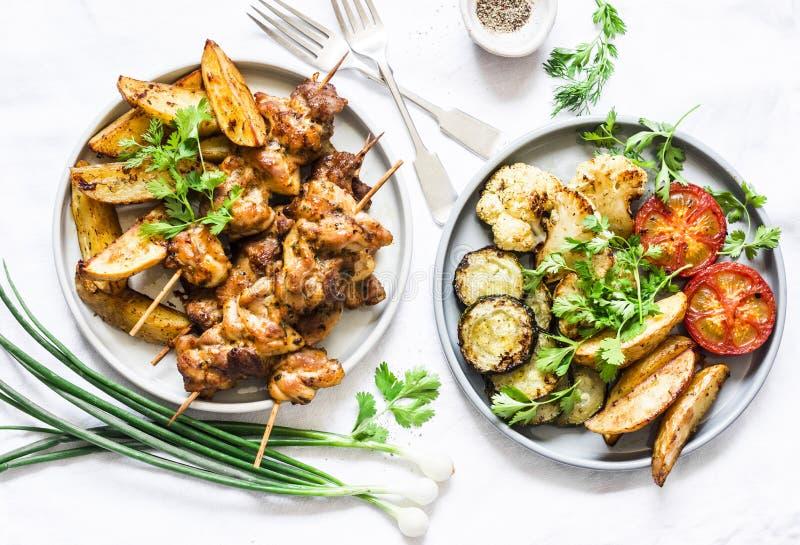 Köttsteknålkebab med bakade potatisar och den grillade zucchinin, tomater, blomkål på en ljus bakgrund, bästa sikt l?ckert arkivfoton