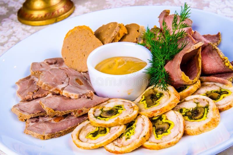 Köttuppläggningsfat med skivad skinka, kallt kokt griskött, rullande välfylld höna som är seitan royaltyfri bild