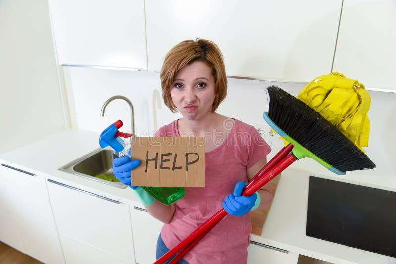 Küche der Frau zu Hause in den Handschuhen mit dem Reinigungsbesen und -mop, die um Hilfe bitten lizenzfreie stockfotos