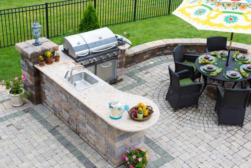 Küche im Freien und Speisetisch auf einem gepflasterten Patio lizenzfreie stockfotos