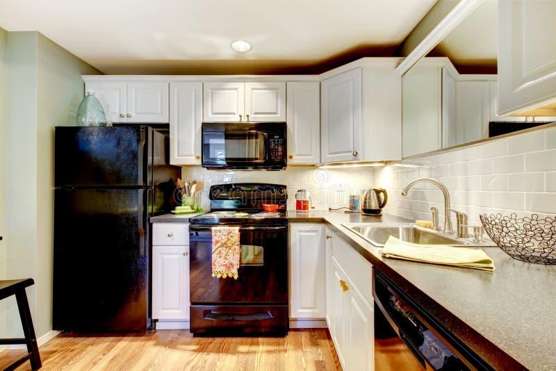 Küche mit schwarzem Kühlschrank, Ofen, Ofen und grauem Zähler stockfotografie