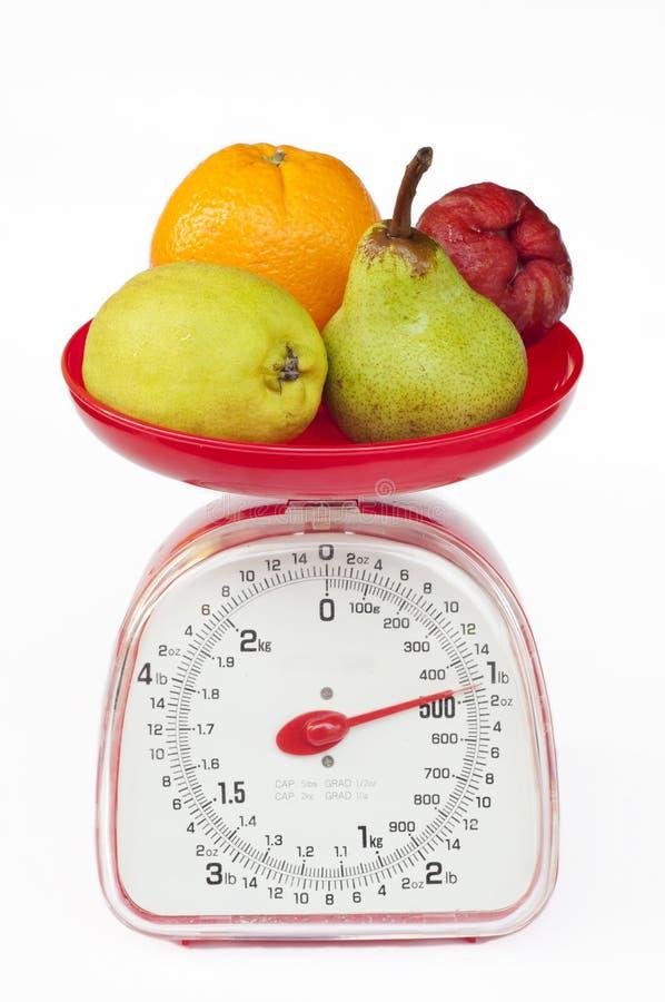 Küchegewichtskala mit Verschiedenartigkeitfrucht stockfotografie