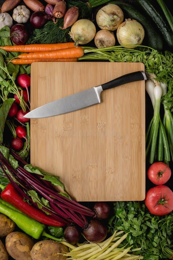 Küchen-Chef Knife auf hölzernem Schneidebrett mit Frischgemüse lizenzfreie stockbilder
