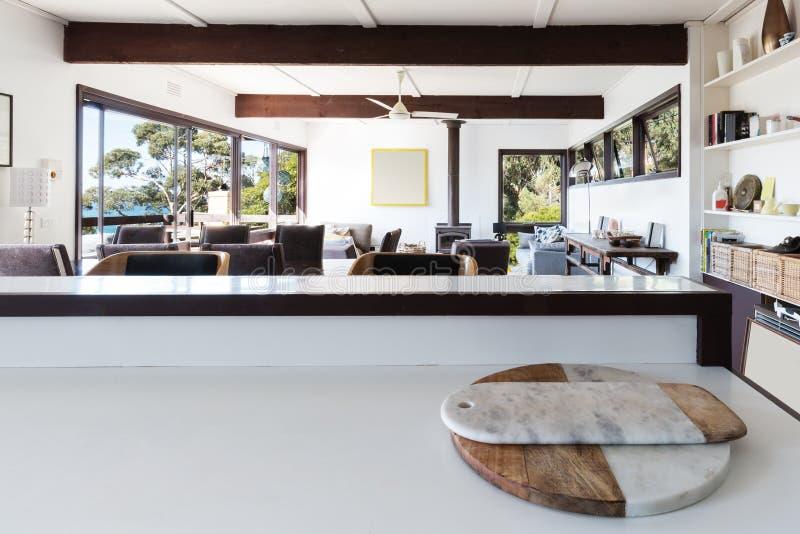 Küchenbank, die zum Großraumwohnzimmer im Retro- Strand ho schaut stockfotografie