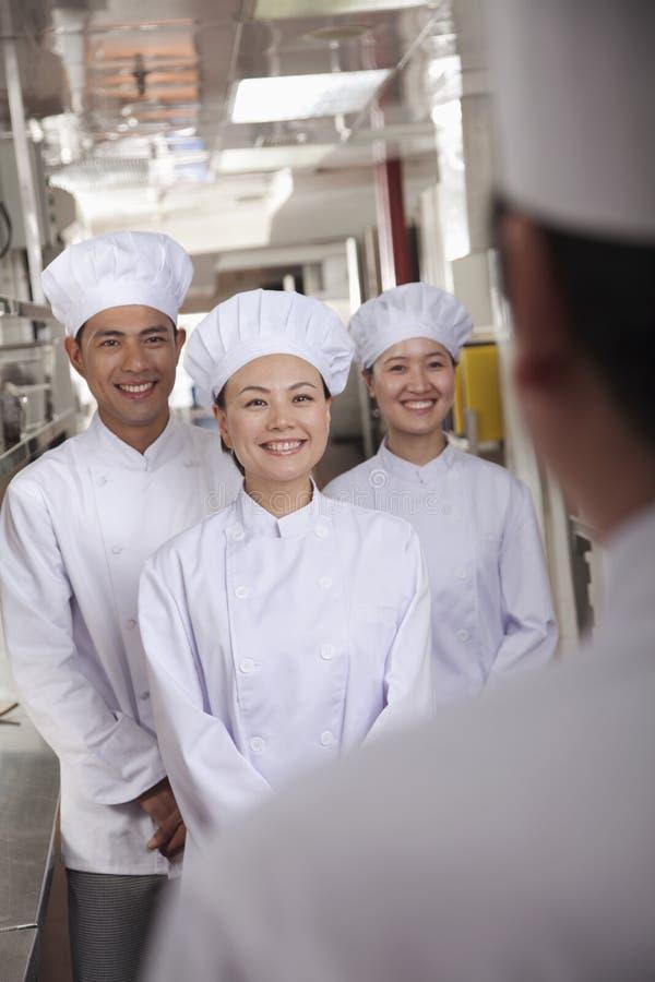Küchenchef Speaking zu den Assistenten lizenzfreie stockbilder